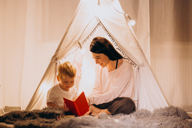 mother-with-son-sitting-cozy-tent-with-lights-home-christmas_1303-12292